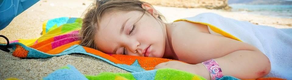 kind slaapt op strand