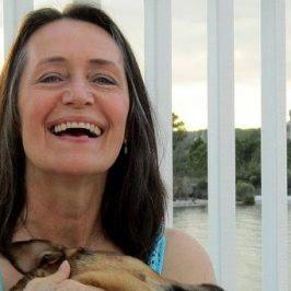 Een lachende vrouw met een hond op schoot