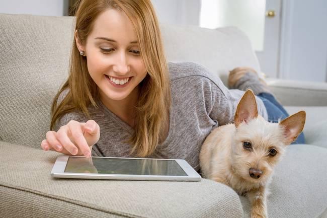 Een vrouw die met haar hond op de bank ligt met een tablet
