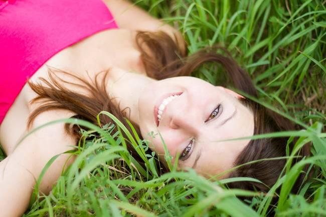 Vrouw die ontspannen in het gras ligt