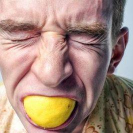 Een man die heel hard op een citroen bijt