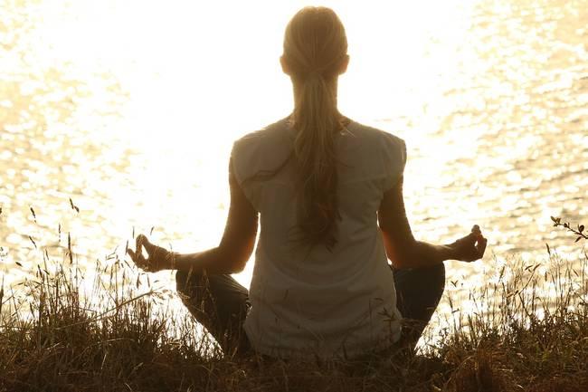 Een vrouw die bij het water aan het mediteren is