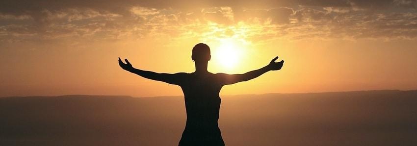 Een man die bij zonsondergang met zijn armen wijd staat