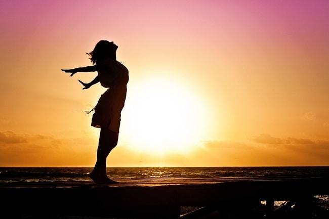 Een vrouw die bij het water staat met haar armen wijd