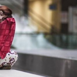 Een vrouw met een rood kussen op een openbare bank
